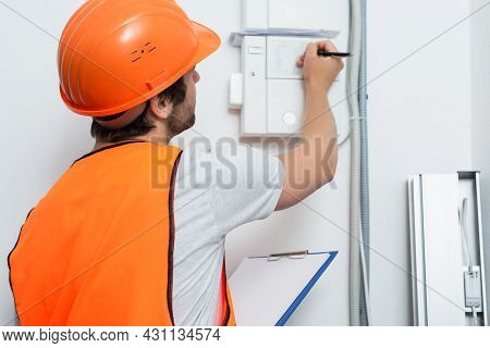 Young Workman With Clipboard Writing On Switchboard