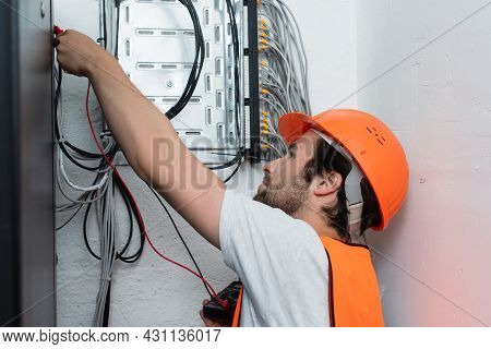 Side View Of Workman Holding Electrical Tester Near Switchboard
