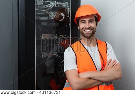 Positive Workman In Safety Vest Standing With Crossed Arms Near Switchboard