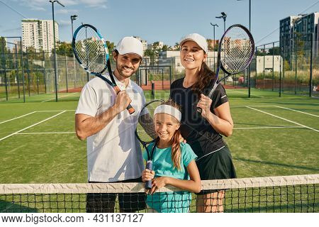 Sporty Family Playing Tennis. Happy Tennis Family Posing On Green Tennis Court Outdoor With Rackets