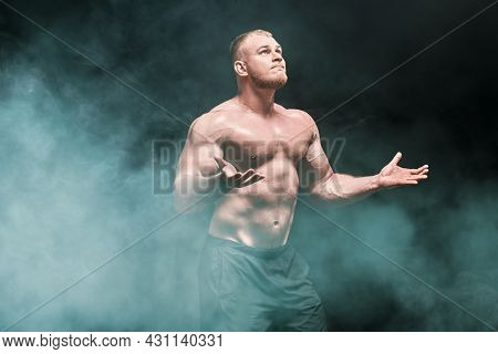 Professional sports, champion. A man weightlifter stands, looking up at the light and raising his arms in tension. Bodybuilding and weightlifting. Studio portrait on a black background.