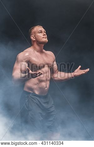 A man weightlifter stands, looking up at the light and raising his arms in tension. Professional sports, champion. Bodybuilding and weightlifting. Studio portrait on a black background.