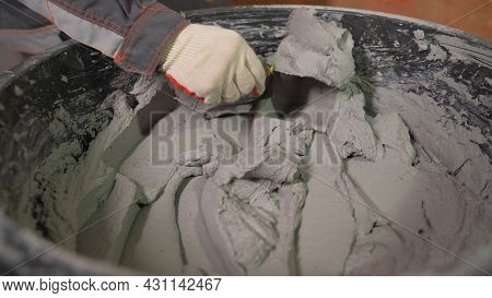 Worker Scooping Mixed Mortar In A Bucket To Tiled. Close-up Of A Hand With A Spatula And Mortar In A