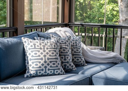 Close Up Of Patio Furniture In Modern Screened Porch, Summertime Woods In The Background.