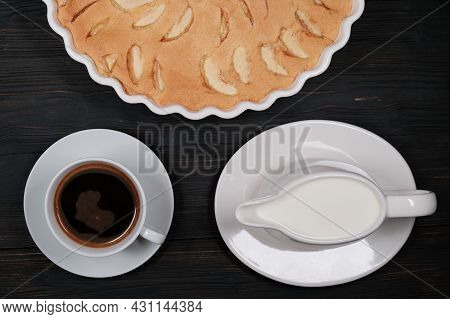 Apple Pie And Cup Of Coffee And Creamer. Homemade Cakes Of Ripe Apples On A Black Wooden Background.