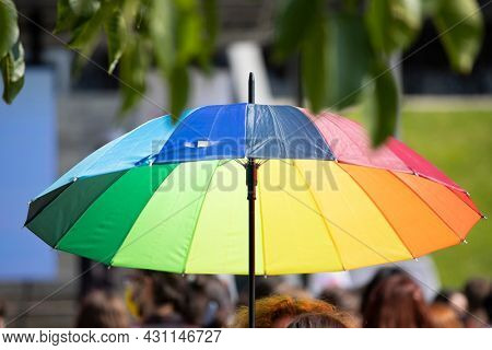 People hold rainbow umbrellas during a LGBTQ gay pride protest.