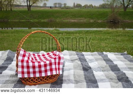 Picnic Basket On A Gray Checkered Blanket Near The River With Copy Space. Outdoor Picnic Concept