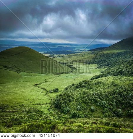 Landscape of green mountains of Massif central, auvergne cloudy day, puy-de-dome, France