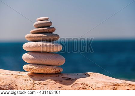 Balanced Pebble Pyramid On The Beach On A Sunny Day. Abstract Sea Bokeh On The Background. Selective