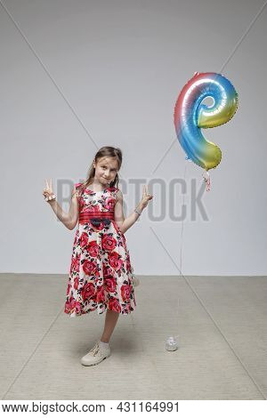Happy Preteen Girl With Long Hair In Festive Dress Dances Carefree Over White Pastel Background, Bir