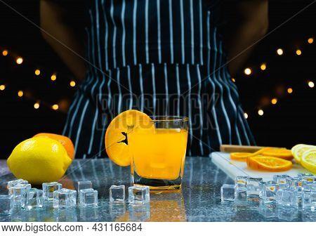 Man Prepare Orange Juice, Slice Fresh Orange In Glass Near Fresh Lemon, Orange, Ice On Table, Barten