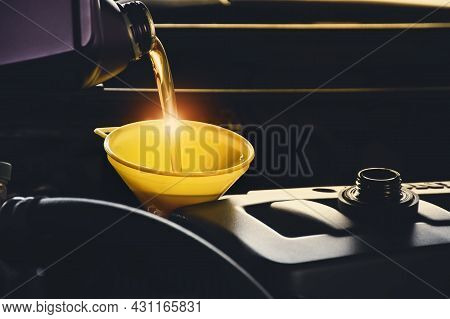 Mechanic Man Pouring Lubricant Oil To Car Engine In The Repair Garage
