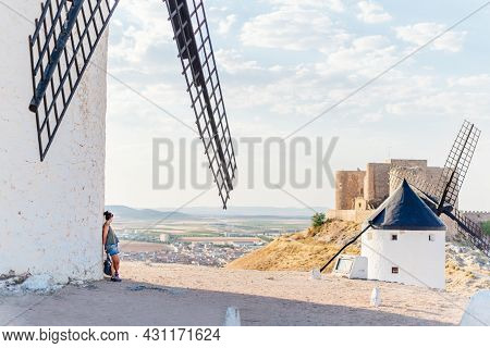Woman Leaning Against The Facade Of A Windmill While Contemplating The Landscape