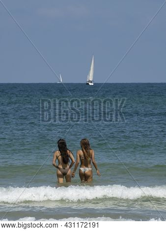 Two Young Women Standing In Shallow Sea Water On A Clear, Sunny Day, With Sailboats In The Horizon.