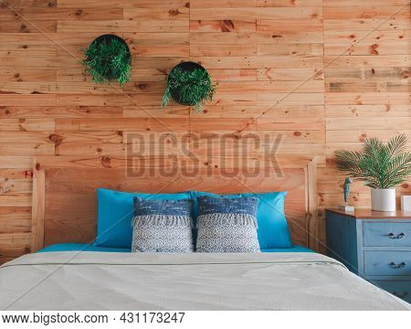 The Wooden Bedroom Interior Features Blue Bedding And Pillows And White Blankets And Potted Plants T