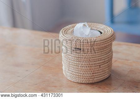 A Light Brown Wicker Basket With White Tissue Paper Inside And Placed On A Light Brown Wooden Table.