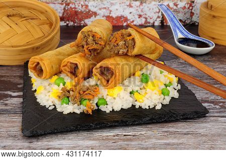 Chinese Crispy Duck And Vegetable Filled Spring Rolls With Egg Rice On A Slate Serving Board