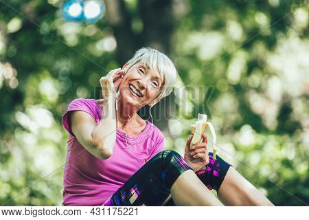 Senior Woman Exercising In Park While Listening To Music. Mature Woman Eat Banana Resting After Exer