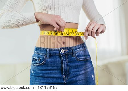 Young Girl With Perfect Waist With A Measuring Tape In Hands