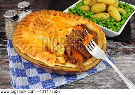Beef Steak Pie In A Glazed Shortcrust Pastry Case With A Pastry Leaf Decoration Served With New Pota