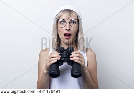Surprised Young Blonde Woman With Binoculars On A Light Background