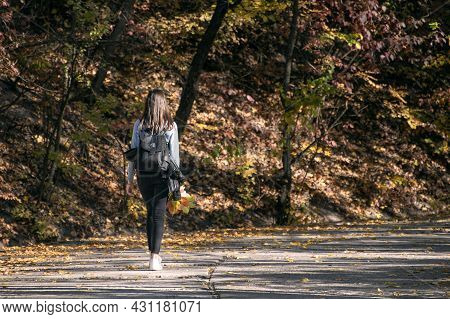 Sad Young Woman Is Walking Along The Alley Of The Autumn Park. Young Lonely Girl In The Forest. Back