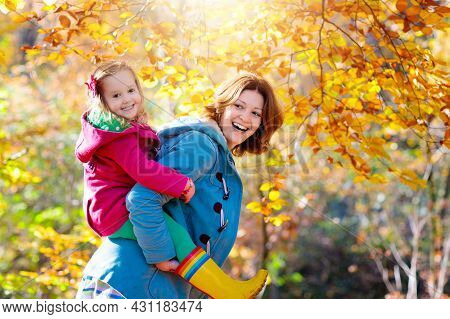 Mother And Child Play In Autumn Park. Mom And Kid Walk In The Forest On A Sunny Fall Day. Children P