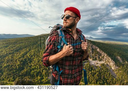 A Bearded Traveler With A Backpack On The Top Of A Mountain. Portrait Of A Traveler In A Red Cap And