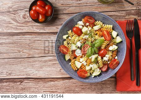 Italian Pasta Fusilli Tricolore With Cherry Tomatoes, Zucchini And Feta Cheese In A Blue Shallow Bow