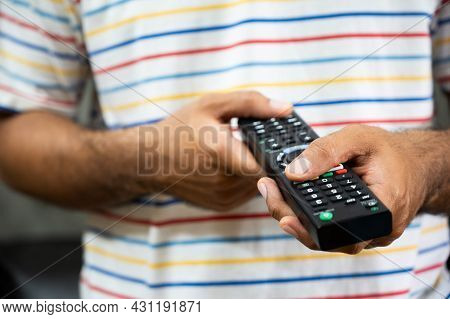 Young Man Holding Television Remote Control. Hands Pointing To Tv Set And Turning It On Or Off Selec