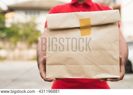 Postman In Red Uniform Holding Package. Delivery At Home
