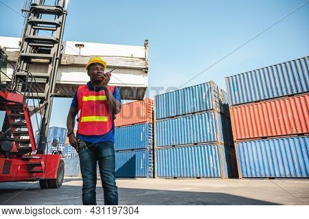 Black Foreman Worker Working Control The Crane And Forklift At Container Cargo Harbor To Loading Con