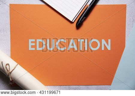 Education Text On Orange And Baby Blue Background Flat Lay Concept. Suitable To Used As Title Cover