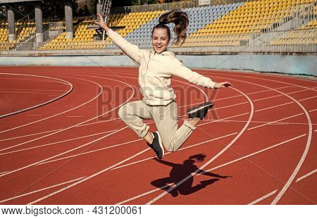 Energetic Girl Child Jump At Athletics Track Physical Education Outdoors, Sport