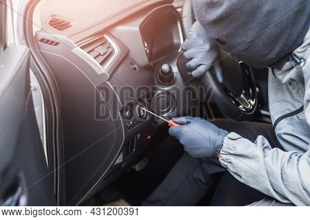 The Thief Uses A Screwdriver Stealing A Car. The Vehicle Insurance Concept.