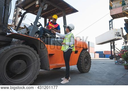 Black Foreman Worker Driving Forklift Checking At Container Cargo Harbor To Loading Containers. Afri