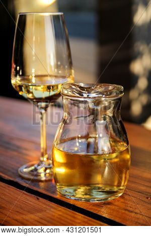 Bottle Of White Wine And Glass On Wooden Table Top. Glass Of Chilled White Wine On Table Near The Be