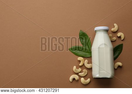 Vegan Milk And Cashew Nuts On Brown Background, Flat Lay. Space For Text