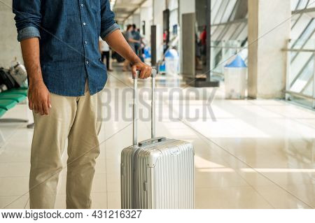 A Male Traveler Wearing A Gray Hat Preparing To Travel He Has A Trolley Bag He Stands At A Large Air