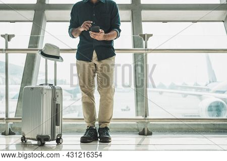 Tourists Are Checking Tour Programs From Their Smartphones At The Airport.