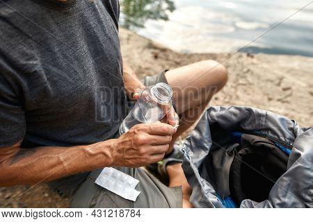 Selective Focus On Pills For Distillation Water And Open Bottle In Male Hands Near Lake In Sunny Nat