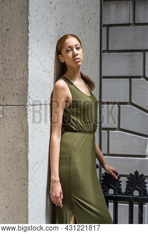 Dressing In A Green Tank Dress, One Hand Resting On Head,  A Young Black Girl Is Lean On Wall And Th