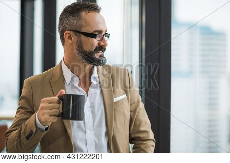 Young Handsome Business Bearded Man Drinking Cup Of Coffee Standing Near Window And Look Outside In