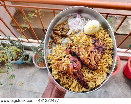 Male Hands Holding A Silver Plate Filled With Chicken Biryani, Two Tandoori Chicken, One Boiled Egg