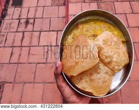 South Indian Male Holding A Plate Filled With Poori Or Puri With Potato Masala. Isolated On Red Back