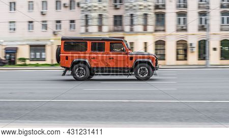 Land Rover Defender 110 Is Driving On Moscow Streets With Blurred Background. Fast Moving Orange Col