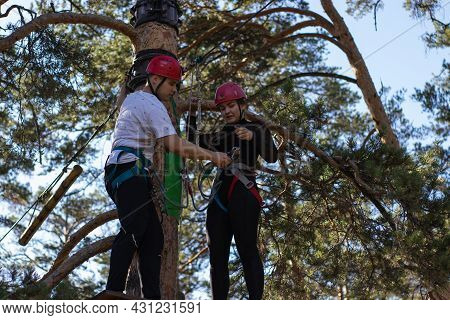 Chelyabinsk Russia - 07 25 2021. Young People In Outfit Go Through A Suspended Forest Extreme Track.