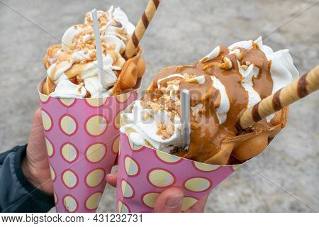 Closeup Outdoor Shot Of Two Bubble Waffles, Gofry Babelkowe, With Lots Of Ice Cream In Pink Paper Co