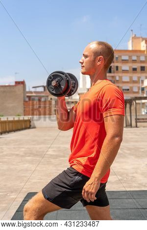 Vertical Shot Of Handsome Muscular Man Lifts Weight Outdoor, Gets Ready For Weight Lifting Training,