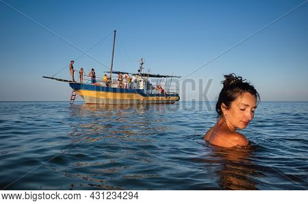 Relaxation And Healthy Lifestyle. Young Beautiful And Emotional Woman Swims In The Sea On A Sunny Da